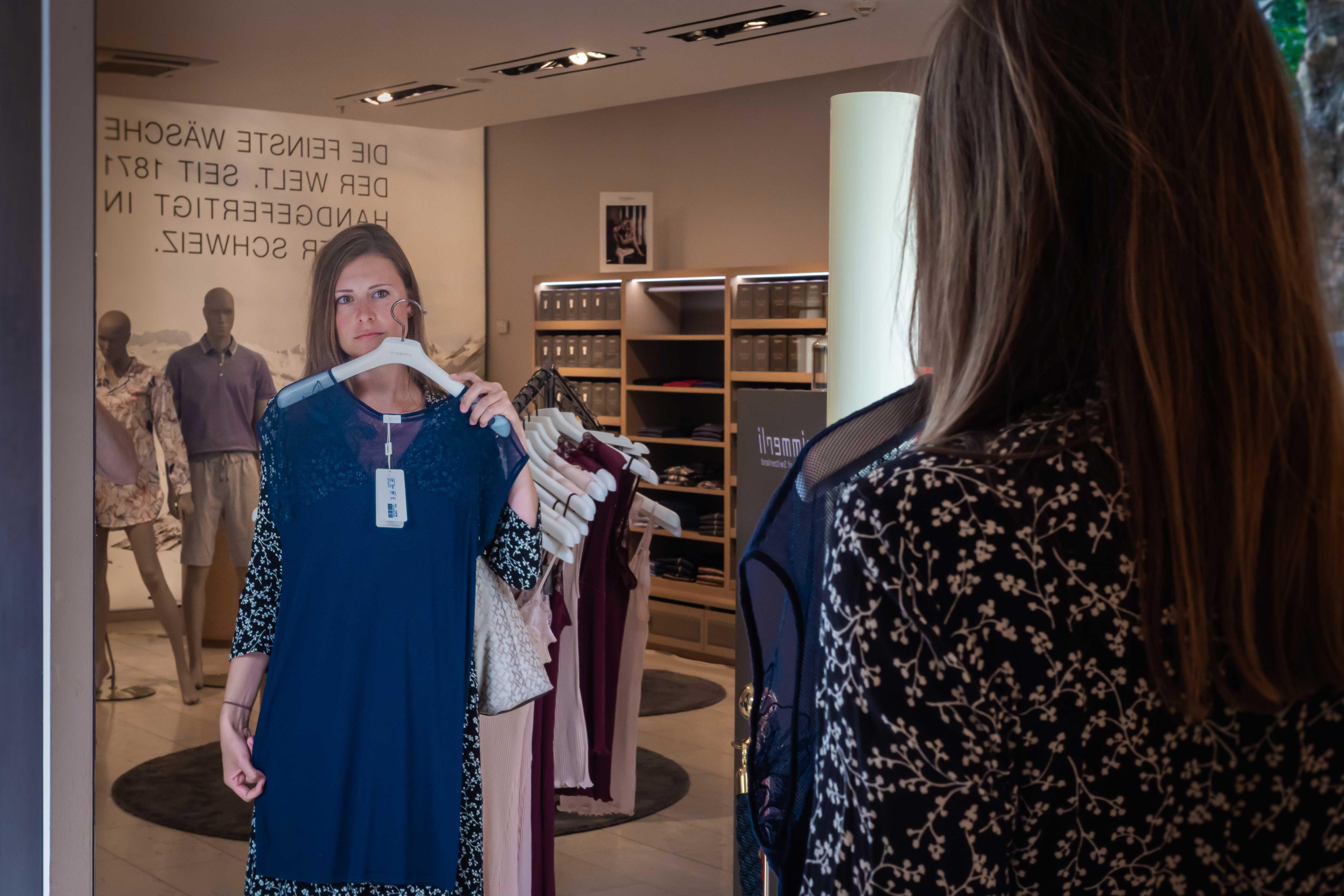 Frau steht vor Spiegel und hält sich Kleid vor die Brust