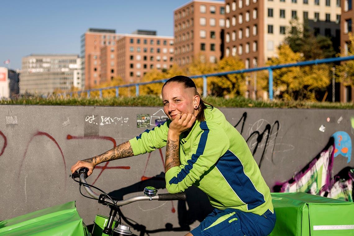 PIN-Zustellerin auf dem Fahrrad vor Wohnsiedlung lächelt in Kamera