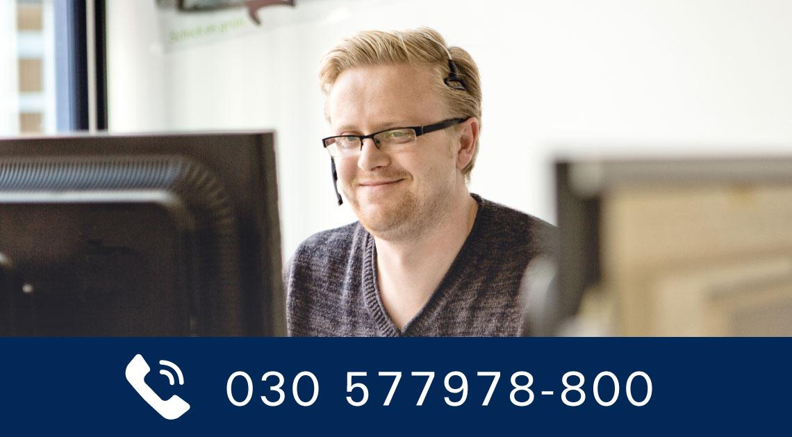 Servicemitarbeiter mit Headset am Computer