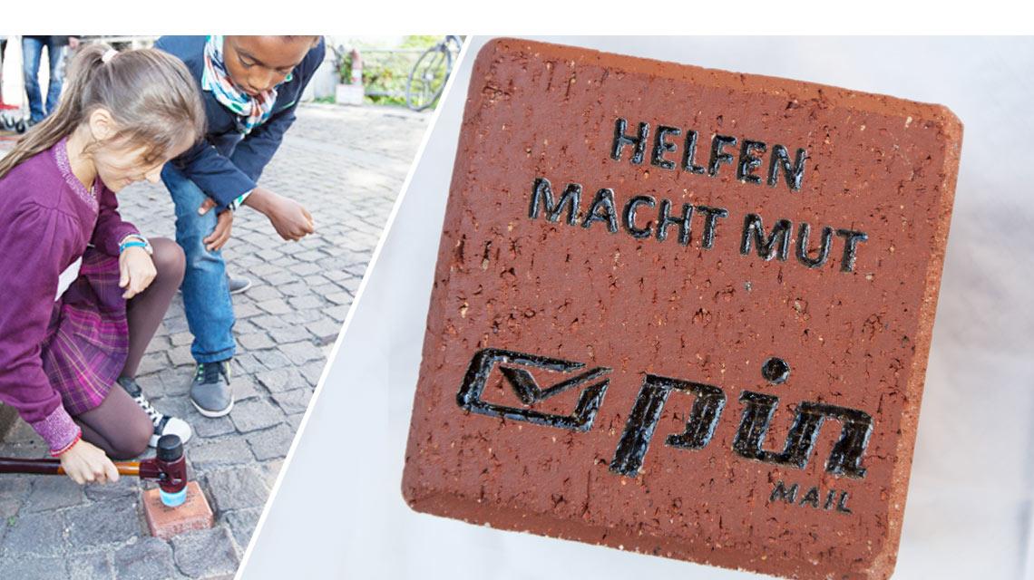 """PIN-Spendenstein - rot mit der Aufschrift """"Helfen macht Mut"""" und dem PIN Logo darunter"""