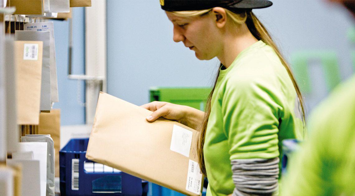 PIN Zustellerin im Depot sortiert einen Maxibrief in das Blocksortierregal