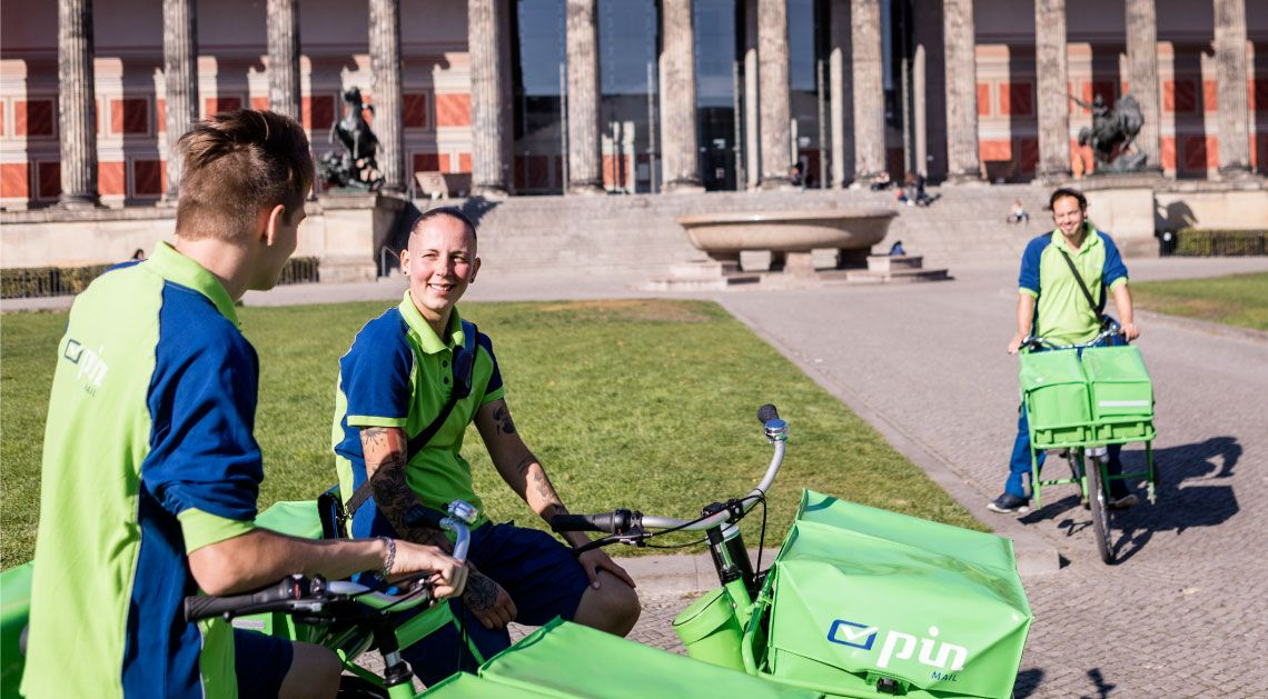 PIN Zusteller auf dem Fahrrad vor dem Berliner Reichstag