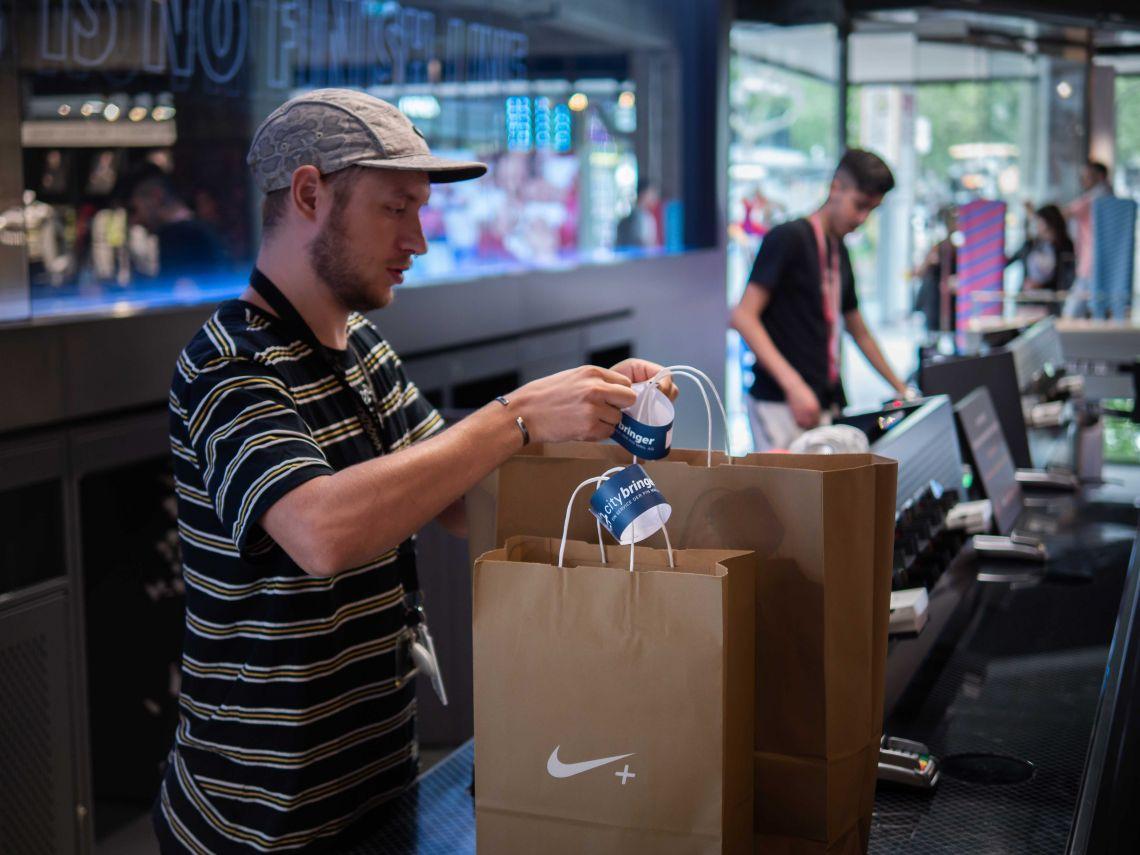 Nike-verkäufer bestellt citybringer und versiegelt die Tüten mit Baggage tag
