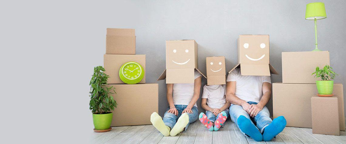 Familie mit Kartons über dem Kopf sitzt vor einer grauen Wand
