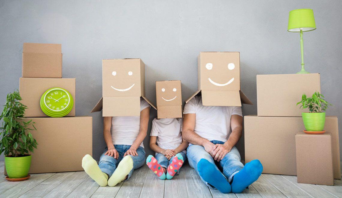 Familie mit Umzugskartons auf dem Kopf sitzt vor einer grauen Wand