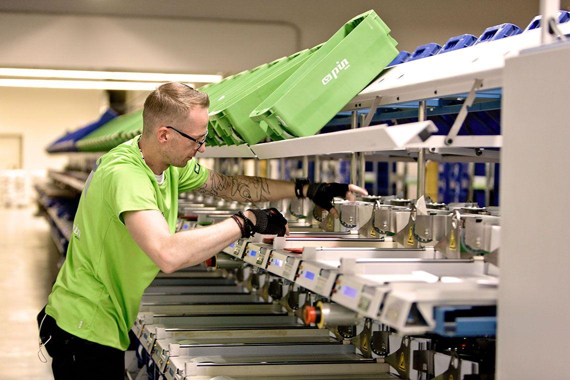 PIN-Mitarbeiter nimmt ein Bündel Briefe aus einer großen Sortiermaschine