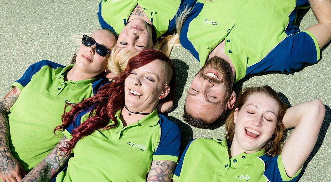 Fünf PIN-Mitarbeiter/innen liegen Kopf an Kopf auf dem Boden
