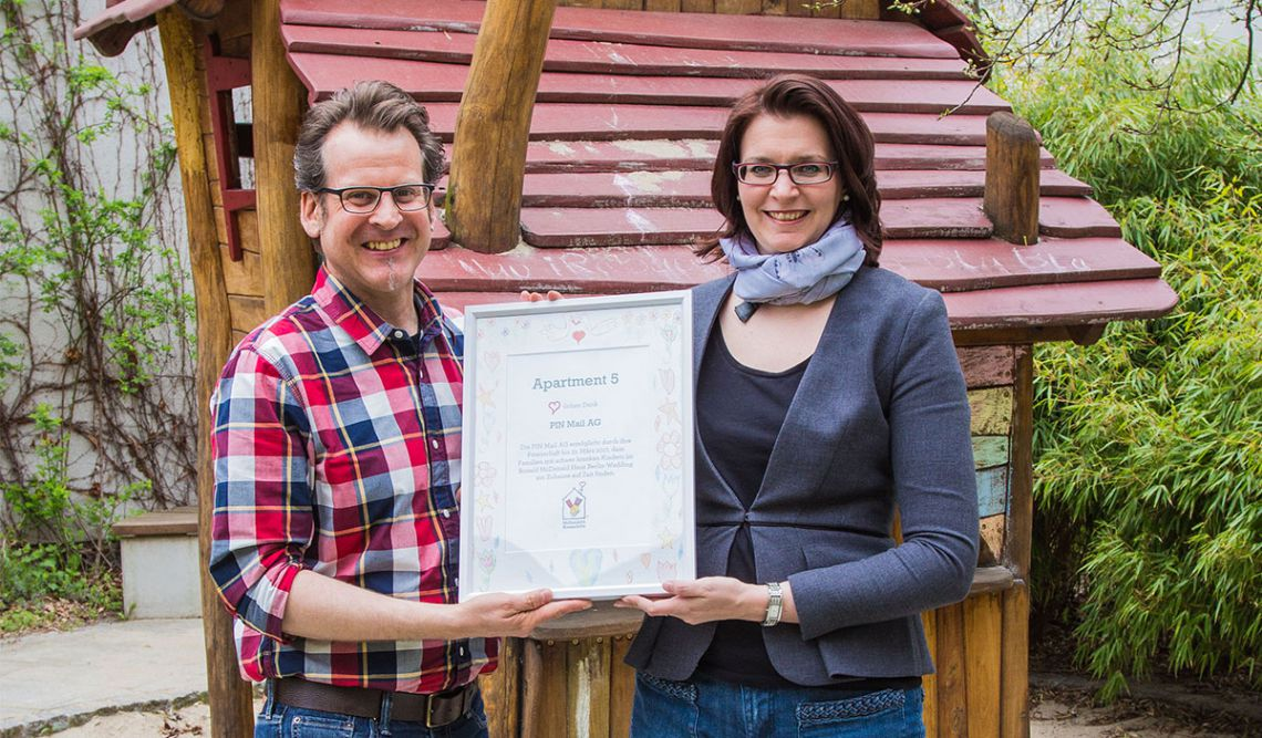 Kathleen Fink und Peter Kaiser, Mitarbeiter der PIN Mail AG, präsentieren stolz die Patenschaftsurkunde für das Apartment Nr. 5 des Ronald McDonald Hauses Berlin-Wedding
