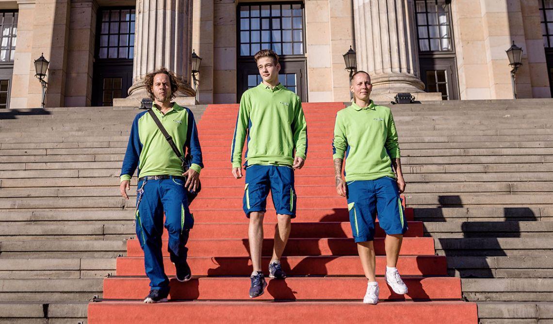 Drei PIN-Zusteller laufen auf einem roten Teppich eine monumentale Treppe runter