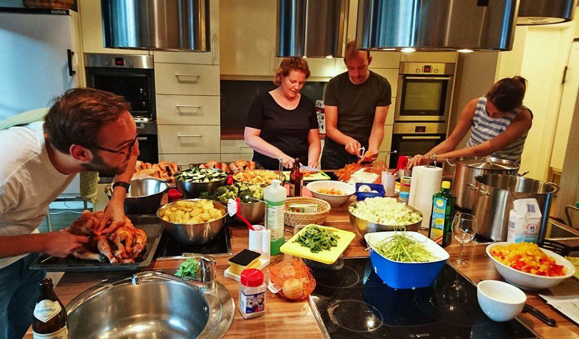 Vier Mitarbeiter der PIN Mail AG beim Vorbereiten unterschiedlicher Zutaten in der Küche des Ronald McDonald Haus Berlin